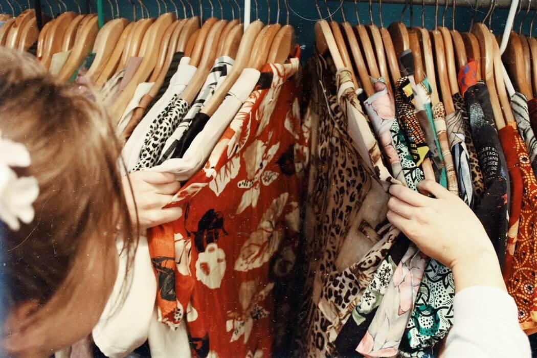 Mujer en una tienda mirando ropa Sonatsounds